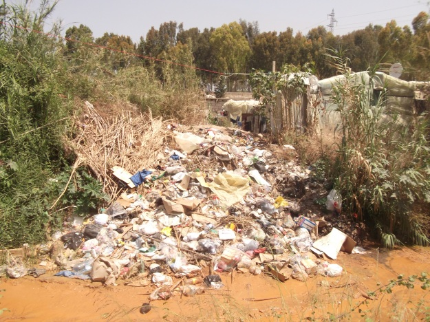 Rubbish piled in sludge moat, Zahrani